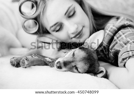 Close up portrait of pretty girl with her little puppy dog in bed happy sleeping or dreaming - stock photo