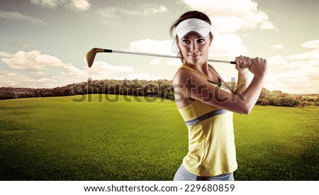 Close up portrait of pretty smiling woman standing with golf club outdoors. Young female golf player wearing sportswear swinging on green field. - stock photo