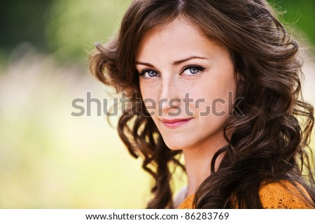 Close-up portrait of pretty young attractive dark-haired curly woman at summer green park. - stock photo