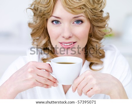 Close-up portrait of pretty young beautiful blond woman with cup of coffee