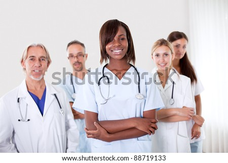 Close-up portrait of pretty young female doctor with colleagues in the background