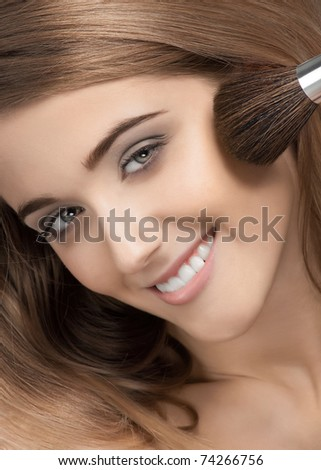 Close-up portrait of pretty young woman applying makeup, isolated on white - stock photo