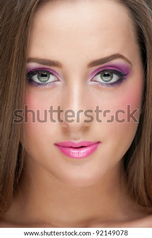 Close-up portrait of pretty young woman with bright lilac make-up
