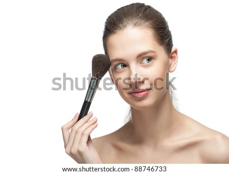 Close-up portrait of pretty young woman with brush for makeup, isolated on white