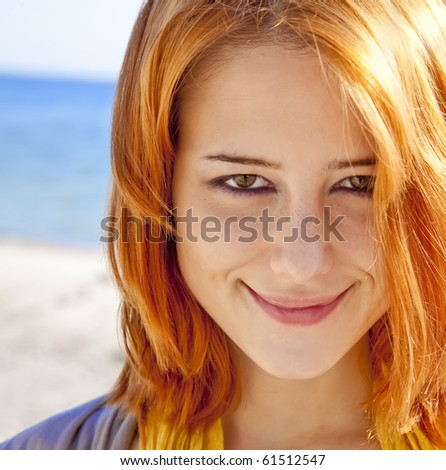 Close-up portrait of red-haired girl at outdoor with blue sea at background.