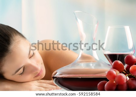 Close up portrait of red wine decanter and bunch of grapes with woman in background.Young girl laying in wine spa.