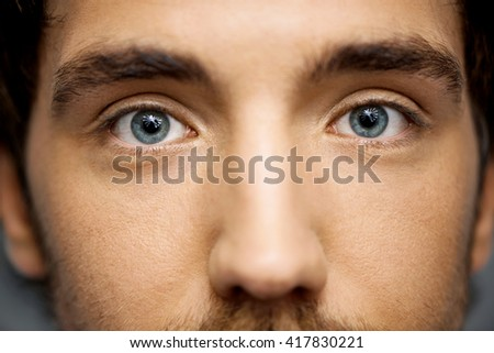 Close up portrait of relaxed handsome young man with grey eyes staring at camera. Studio, isolated on grey background. - stock photo