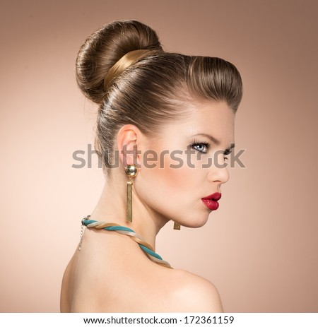 Close-up portrait of retro red lips stylish woman wearing golden luxury jewelery. Beautiful blond female model with vintage hairstyle, glossy earrings and necklace posing in studio.   - stock photo