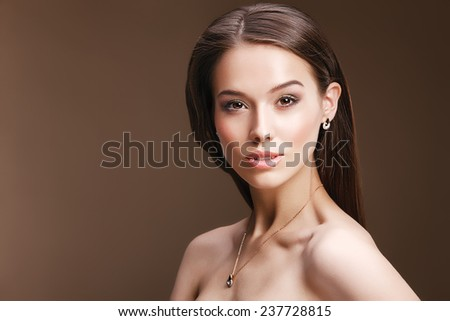 Close-up portrait of retro red lips stylish woman wearing golden luxury jewelery. Beautiful female model with vintage hairstyle, glossy earrings and necklace posing in studio. - stock photo