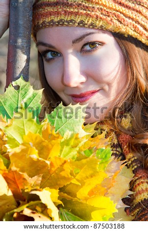 close up portrait of russian autumn woman in knitted beret with  maple leaves on nature. More of this series on my portfolio ! - stock photo