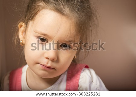 Close up portrait of sad little girl. Expressive little girl, melancholic, thinking away, studio shot on brown background - stock photo