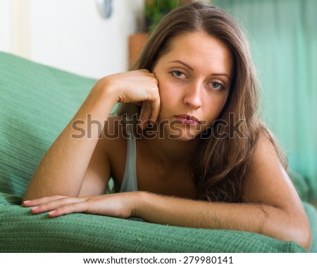 Close up portrait of sad young long-haired girl at home