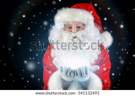 Close-up portrait of Santa Claus blowing on snowflakes. Christmas time. Black background. - stock photo