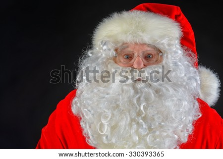 Close-up portrait of Santa Claus over black background. Christmas time.  - stock photo