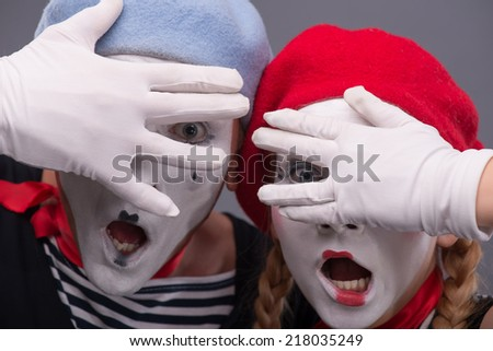 Close-up portrait of scared mime couple with startled faces closing their eyes with their hands and fingers isolated on grey background - stock photo