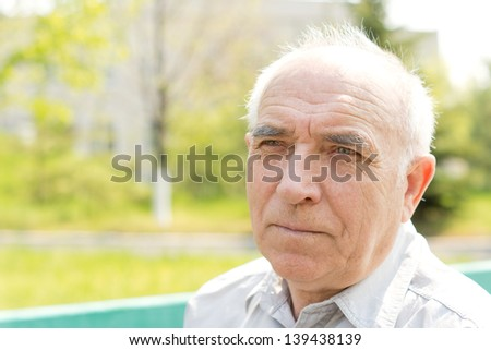Close up portrait of senior bald man looking at something in the park - stock photo