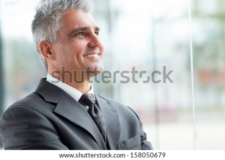 close up portrait of senior businessman looking up - stock photo