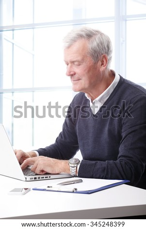 Close-up portrait of senior businessman sitting at office in front of laptop and working on his presentation.