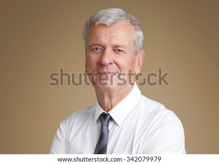 Close-up portrait of senior businessman standing against isolated background while wearing shirt and tie.