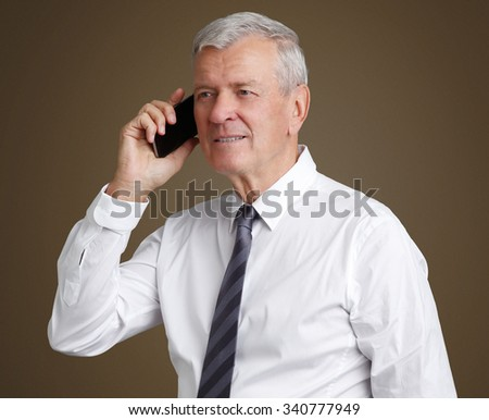 Close-up portrait of senior businessman wearing shirt and tie while standing at isolated background and making call. Old professional man looking away and smiling.