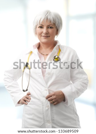 Close-up portrait of senior female doctor standing in the hospital and smiling - stock photo