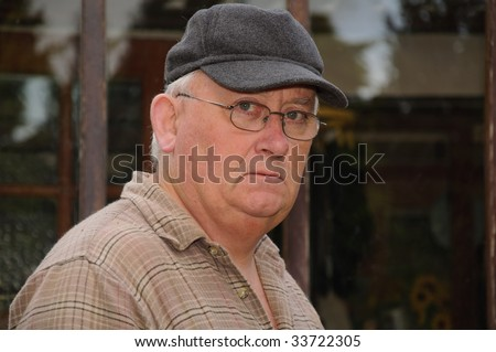 close up portrait of senior male glasses and cap - stock photo