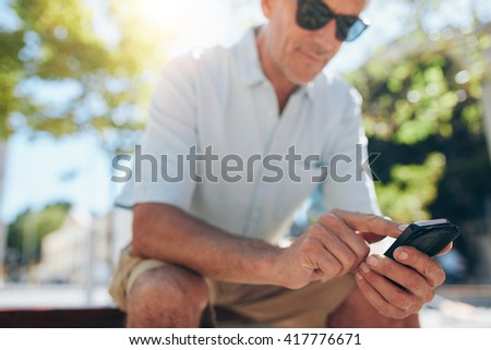 Close up portrait of senior man using cell phone while sitting on a bench in the city on a sunny day. Focus on hands holding mobile phone. - stock photo