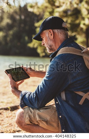 Close up portrait of senior man with backpack sitting by a lake and using digital tab in the forest for navigation. - stock photo