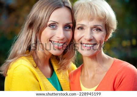 Close up portrait of senior Mother with her adult blond daughter looking at the camera and smiling outdoor - stock photo