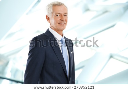 Close-up portrait of senior sales man standing at office while looking at camera. - stock photo