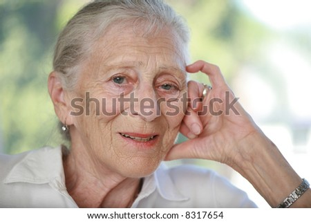 Close-up portrait of senior woman contemplating. Shallow DOF. - stock photo