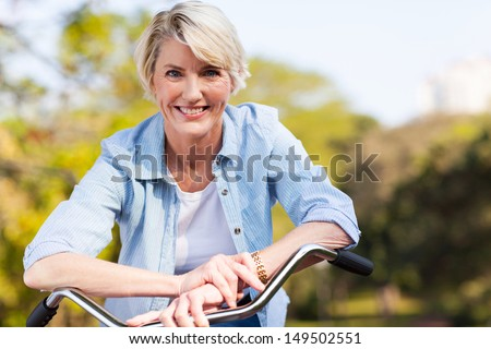 close up portrait of senior woman on a bicycle - stock photo