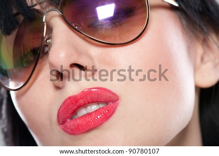 Close-up portrait of sensual and tender woman's face wearing sunglasses - stock photo