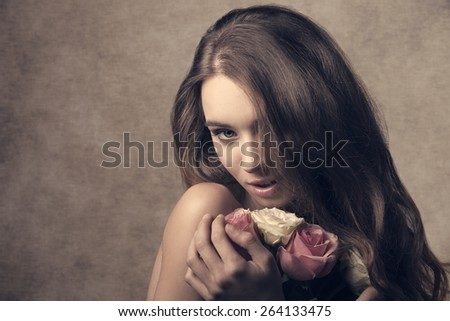 close-up portrait of sensual lady with long hair, taking bouquet of white and pink roses in the hands. Romantic expression and perfect skin, looking in camera   - stock photo