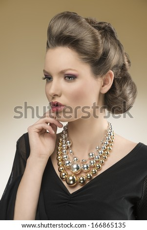 close-up portrait of sensual woman with aristocratic style posing with elegant hair-style and black dress, wearing big bright necklace      - stock photo