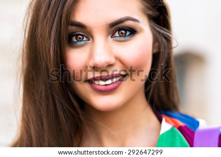 Close up portrait of sensual young beautiful brunette woman, with long hairs perfect skin and trendy bright ,make up, looking on camera, gorgeous smile, soft pastel colors. - stock photo