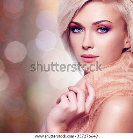 Close-up portrait of sensual young woman in the beige fabric over creative background.