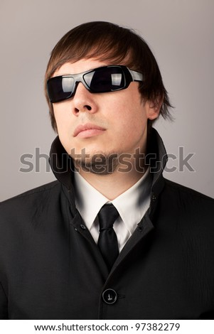 Close-up portrait of serious man in a business suit and sunglasses. On a gray background - stock photo