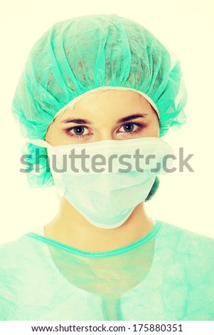 Close-up portrait of serious nurse or doctor in white mask  - stock photo