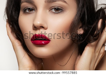 Close-up portrait of sexy caucasian young woman model with glamour dark red gloss lips make-up and purity complexion, beautiful romantic hairstyle. Perfect clean skin. - stock photo