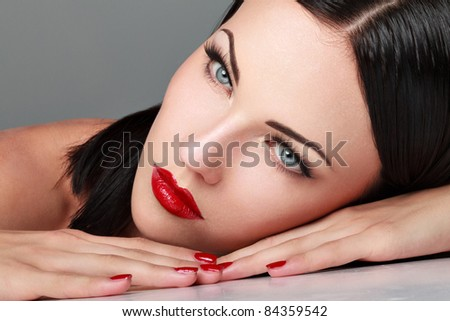 Close-up portrait of sexy caucasian young woman with  make-up and red bright manicure - stock photo