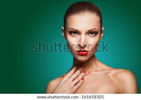 Close-up portrait of sexy caucasian young woman with red glamour make-up and bright manicure over green background - stock photo