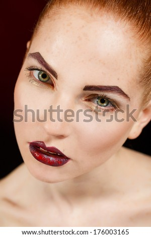 Close-up portrait of sexy european young woman model with glamour make-up and red bright manicure. christmas makeup, bloody red lips with gloss