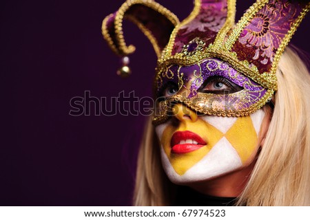 close up portrait of sexy woman in party mask isolated on violet background - stock photo