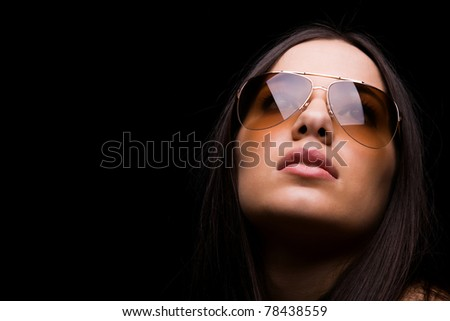 close-up portrait of sexy woman in sunglasses over dark background - stock photo