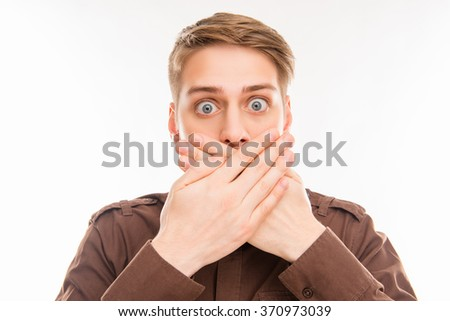 Close up portrait of shocked young man closing his mouth with hand - stock photo