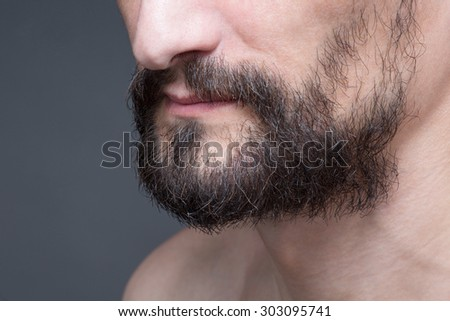 Close-up portrait of short beard and mustache with naked bearded man. Middle-aged man demonstarting his black beard.
