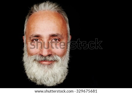 close-up portrait of smiley bearded man over black background with empty copyspace - stock photo
