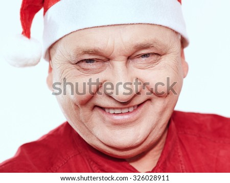 Close up portrait of smiling aged man wearing Santa Claus hat and red shirt against white background - Christmas concept - stock photo