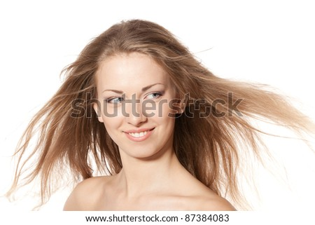 Close up portrait of smiling beautiful blond female with hair lightly fluttering in the wind looking aside over white background